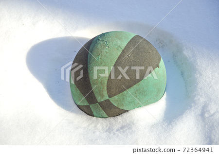 old and aged rubber playing ball on snow in garden 72364941