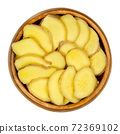 Fresh ginger slices in a wooden bowl. Rhizomes of Zingiber officinale, cut into sections, used as a fragrant spice and as a folk medicine. Close-up, from above, isolated over white, macro food photo. 72369102