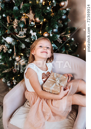 Beautiful little girl with gift near Christmas tree at home 72369914