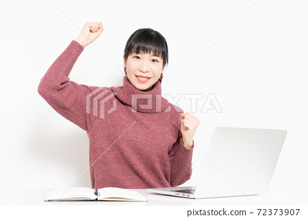 A woman doing a guts pose while using a laptop 72373907