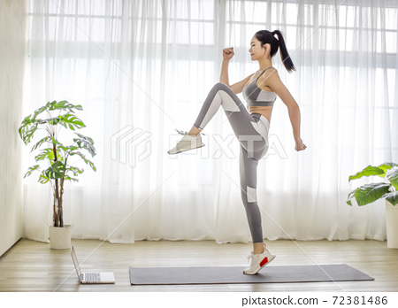 Young  woman in sportswear watching online video with fitness exercises on laptop 72381486
