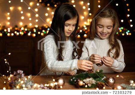 two little child girls make a handmade Christmas wreath 72383279