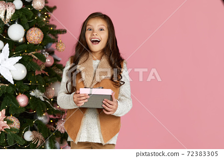 child girl holding Christmas gift box 72383305