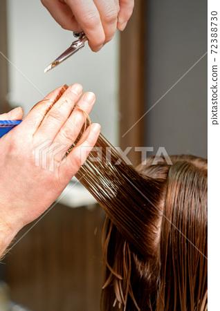 Hairdresser's hands cuts female hair 72388730