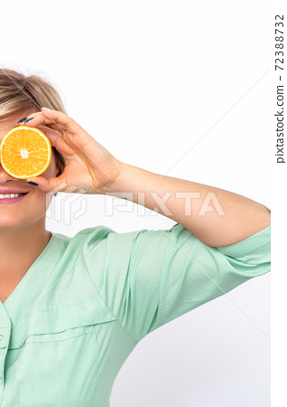Cosmetologist covering eyes with orange 72388732