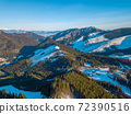 Winter Mountain Peaks and a Valley at a Ski Resort on a Sunny Day. Aerial View 72390516