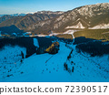 Winter Mountain Peaks and Ski Slopes in Sunny Weather. Aerial View 72390517