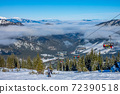 Skiers on the Chair Lift and Light Fog between Peaks 72390518