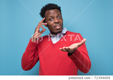 Puzzled african young man having no idea asking what to do. 72394009
