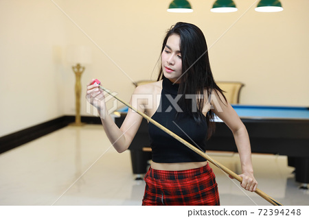 young beautiful asian woman standing on blue pool table with cue and wiping before billiards game begin in club 72394248