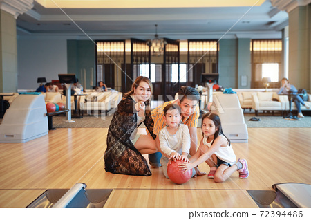 group of happiness asian family father, mother, son and daughter playing bowling in sport club with happy smiling face during holiday vacation 72394486