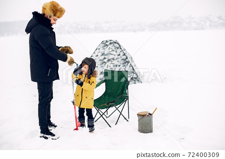Handsome man on a winter fishing with his little son 72400309