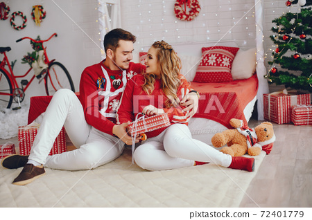 Cute family sitting near Christmas tree 72401779