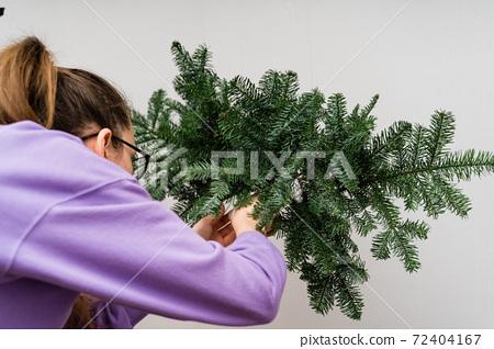 Girl florist with a hanging pine garland. Woman florist decorating. Christmas DIY decoration 72404167