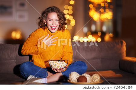 young  delighted cheerful woman with popcorn laughs and watches  christmas movie on  TV   at home in evening  alone. 72404384