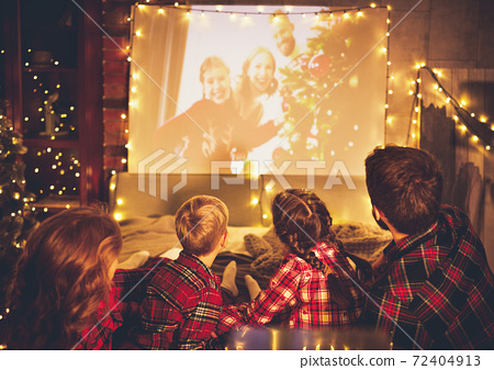 family mother father and children watching projector, TV, movies with popcorn in   christmas evening   at home. 72404913