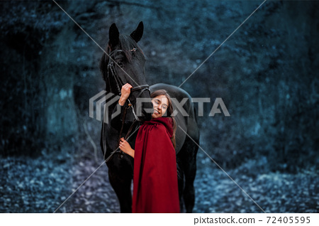 Fabulous portrait of a beautiful young lady with long brown hair, suite with red or burgundy cloak with her black horse in winter 72405595