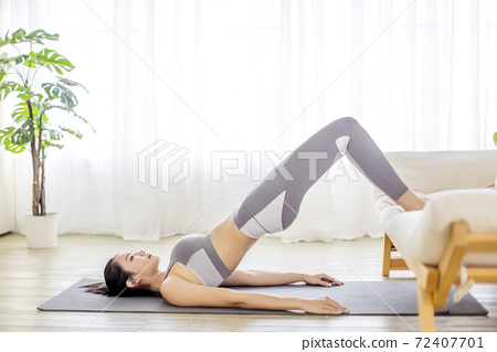young woman in sportswear doing fitness stretching exercises at home 72407701