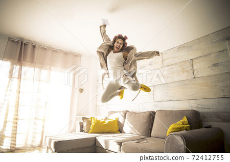 Concept of end quarantine coronavirus covid-19 lockdown stay home time - woman jump with joyful and happiness feeling emotions - concept of success and joy for people 72412755