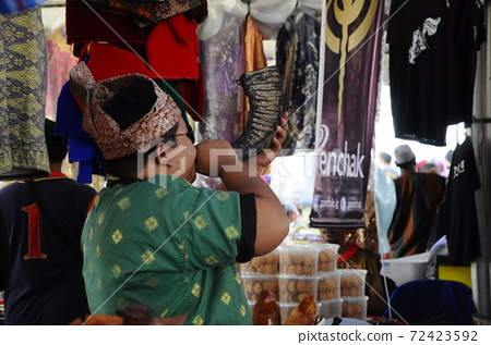 SEREMBAN, MALAYSIA -MAY 01, 2017: A man is blowing a traditional pipe made of buffalo horn. 72423592