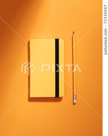 Monochromatic still life with notebook and pencil. 72430487
