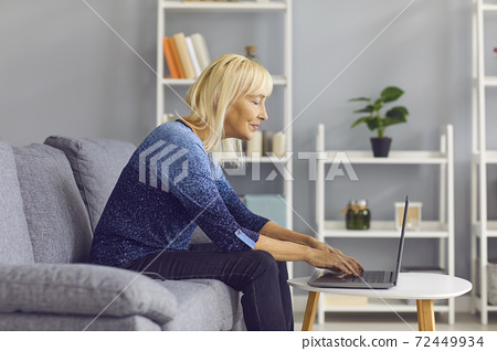 Side view of a mature woman typing on laptop while sitting on her sofa at home. 72449934