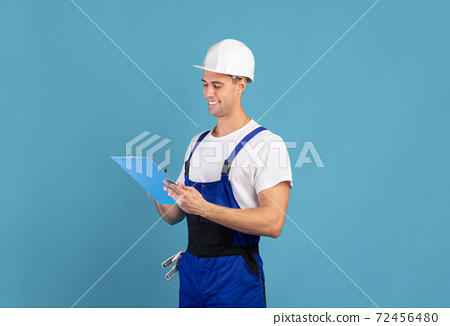 Smiling male repair contractor in coveralls and hardhat writing notes in clipboard 72456480