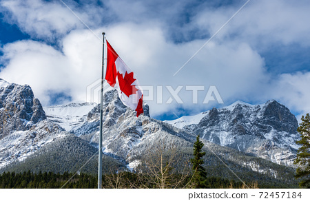 Close up of National Flag of Canada with natural mountains and trees scenery in the background. 72457184