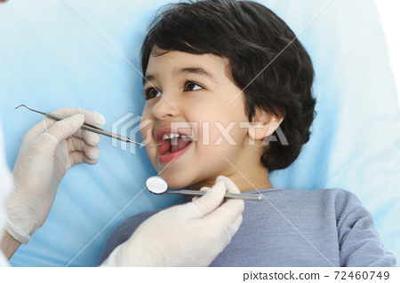 Cute arab boy sitting at dental chair with open mouth during oral checking up with doctor. Visiting dentist office. Stomatology concept 72460749