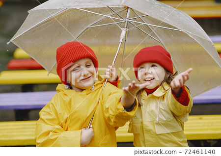Funny kids in rain boots playing in a rainy park 72461140