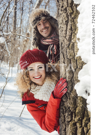Playful couple in the snow hiding behind a tree trunk 72462502