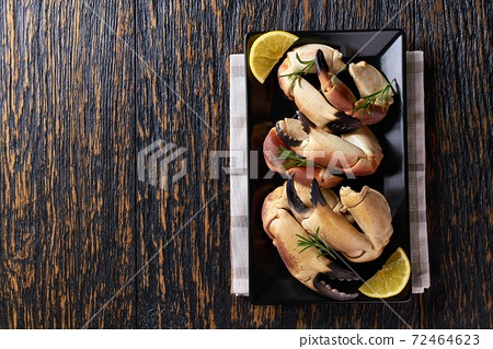 Crab claws in black plate on a wooden table,with copy space for text, top view. 72464623