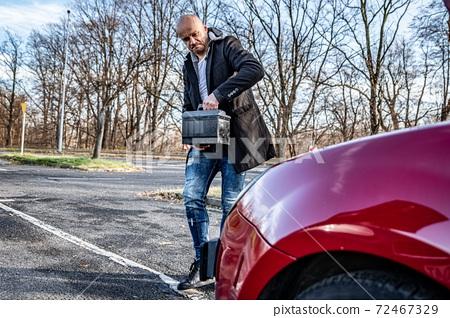 Irradiated man holding car battery. Broken car problem 72467329