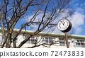 School building clock blue sky cherry tree 72473833