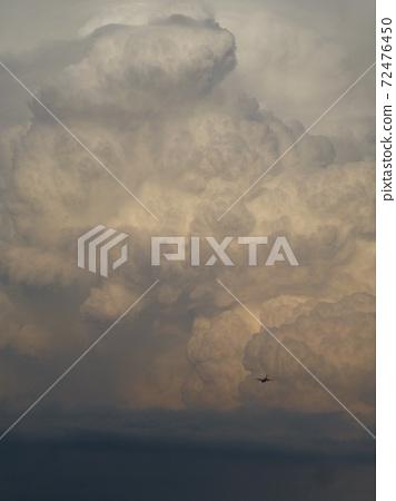 台灣高雄-06.03.2013:軍用運輸機準備飛進積雨雲 72476450