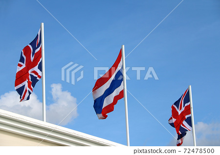 One of Thai flag and two Union Jack flag on bright blue sky background. Blown away by wind. 72478500