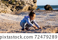 Happy little girl enjoying summer vacation and playing seashells on the beach. 72479289