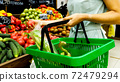 Woman with shopping basket is choosing vegetables in grocery store. 72479294