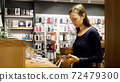 Young woman chooses a new smartphone in an electronics store. 72479300