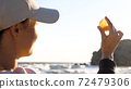 Young woman is holding seashell in hand and looking on sun through shell 72479306