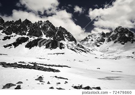 High sunlit rocks, snowy plateau and cloudy sky 72479860