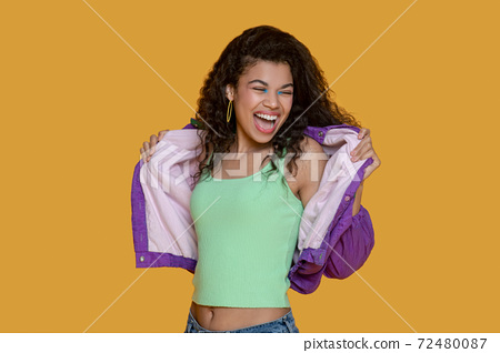 Pretty dark-haired young girl in bright jacket looking happy 72480087