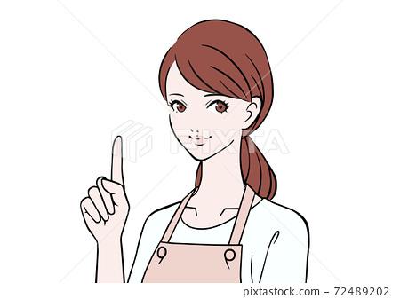 一個圍裙,指著她的手指的女人 72489202