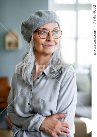 Portrait of senior woman with gray beret standing indoors against dark background. 72494032