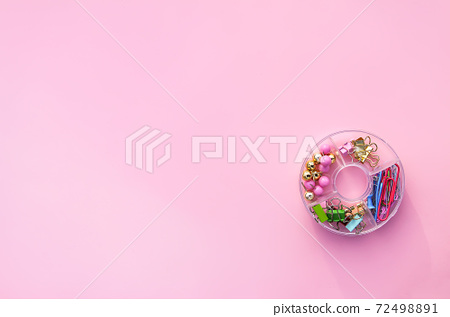 Set of paper clips and buttons in a plastic rouncontainer on a soft pink background 72498891