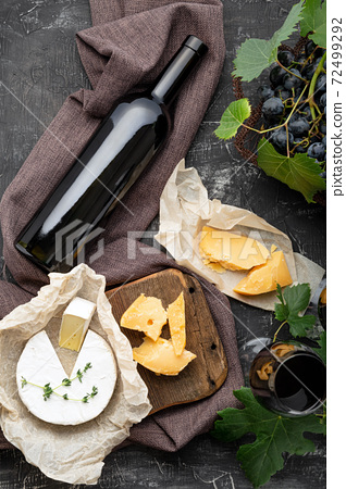 Red wine bottle Camembert cheese and aged cheese, grapes. Wine bar snacks. Wine composition on dark rustic concrete background. Flat lay vertical crop 72499292