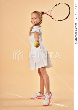 Cheerful cute girl playing tennis and smiling 72499647