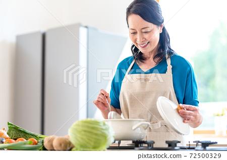 부엌에서 요리하는 노인 여성 72500329