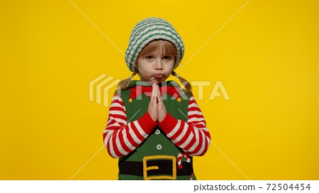 Keeps palms together. Kid in Christmas elf Santa helper costume begs, prays about gifts on New Year 72504454