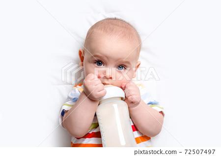 Caucasian baby boy with baby milk bottle.  72507497